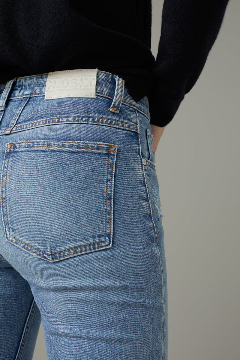 Close up on back pocket of jeans on model.
