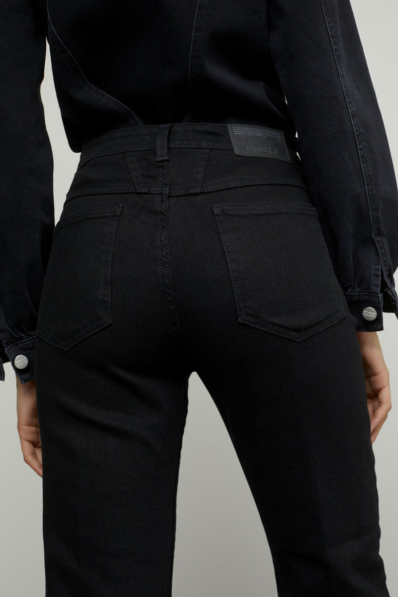 Close up on back pockets of jeans on model.