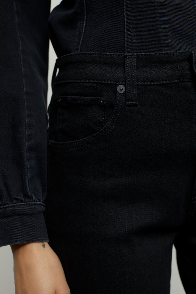 Close up on front waist band and pocket of jeans on model.
