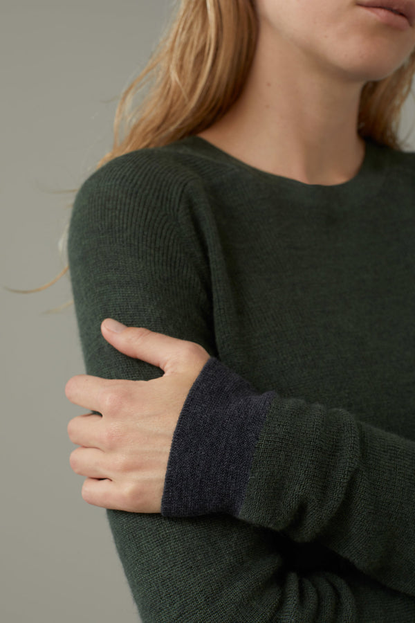 Close up on cuff of sweater on model.