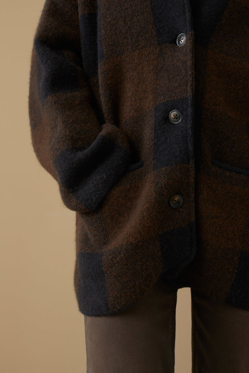 Close up on sleeves and pocket of coat on model.