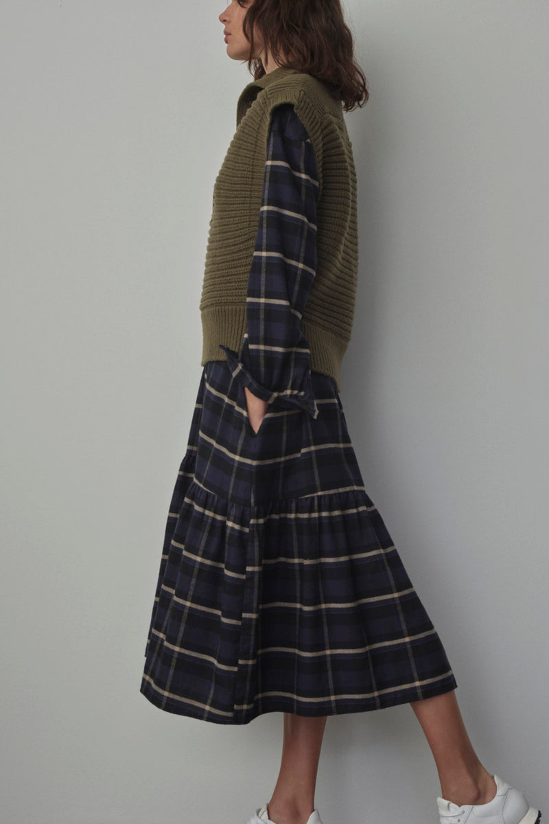Another view of a model wearing the closed sweater vest with a navy, plaid dress.
