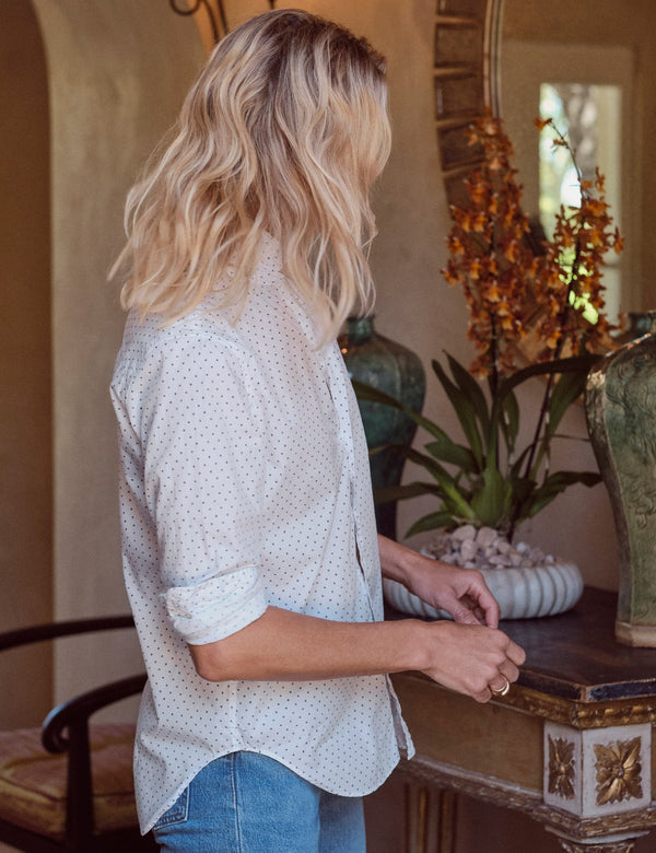 A side view of the Frank cotton shirt in Navy faded dot. The model is wearing the top with a classic blue jean and has the sleeves rolled for a laid back look.