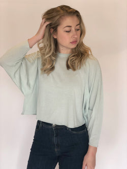 Front of top on model with hand in hair also wearing blue jeans.