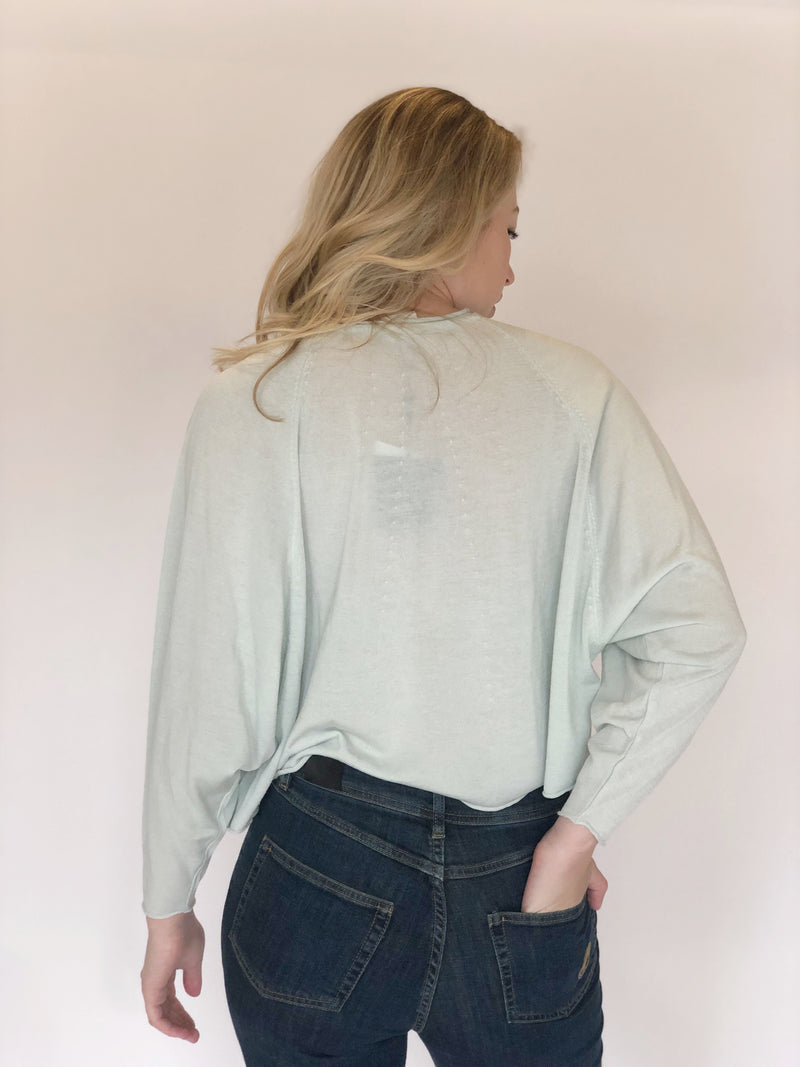 Back of top on model with one hand in her back pocket, also wearing blue jeans.