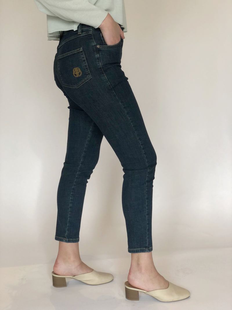 Side of jeans on a model also wearing a blue sweater and ivory slides.