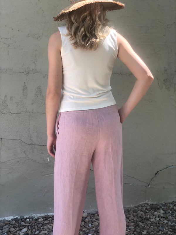 Back of pants on a model also wearing a white tank and hat.