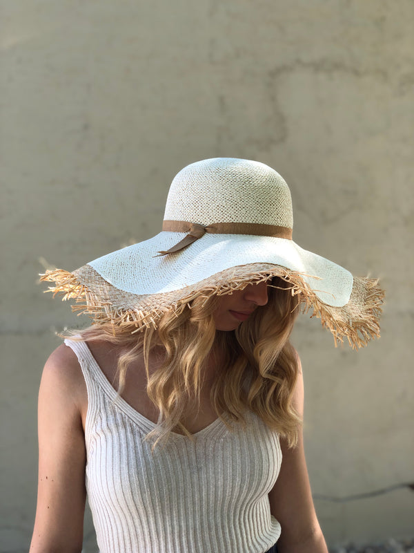 Photo of hat on model looking down wearing a white tank.