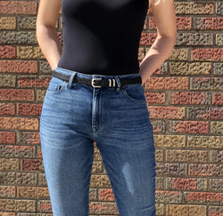 Front of belt pictured on a model wearing a black bodysuit and jeans.