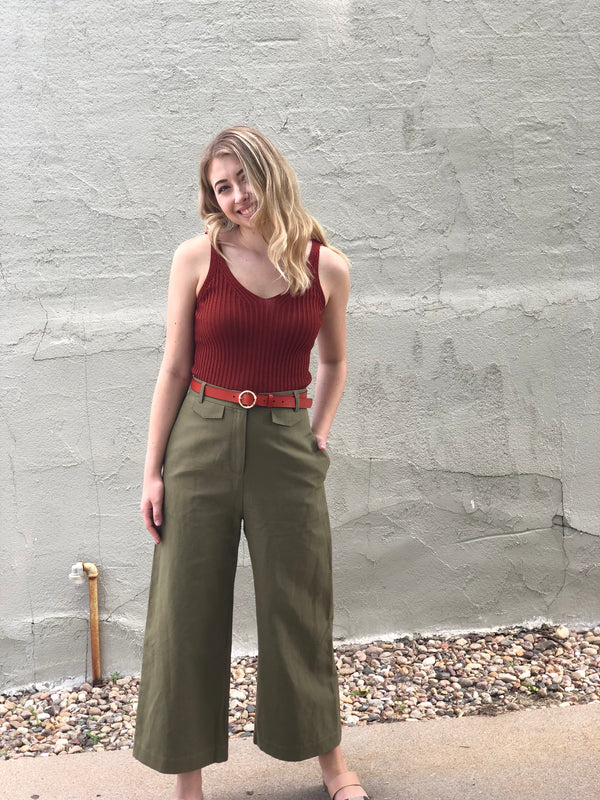 Photo of front of pants on a model outside. Model is wearing a rust colored tank and belt.