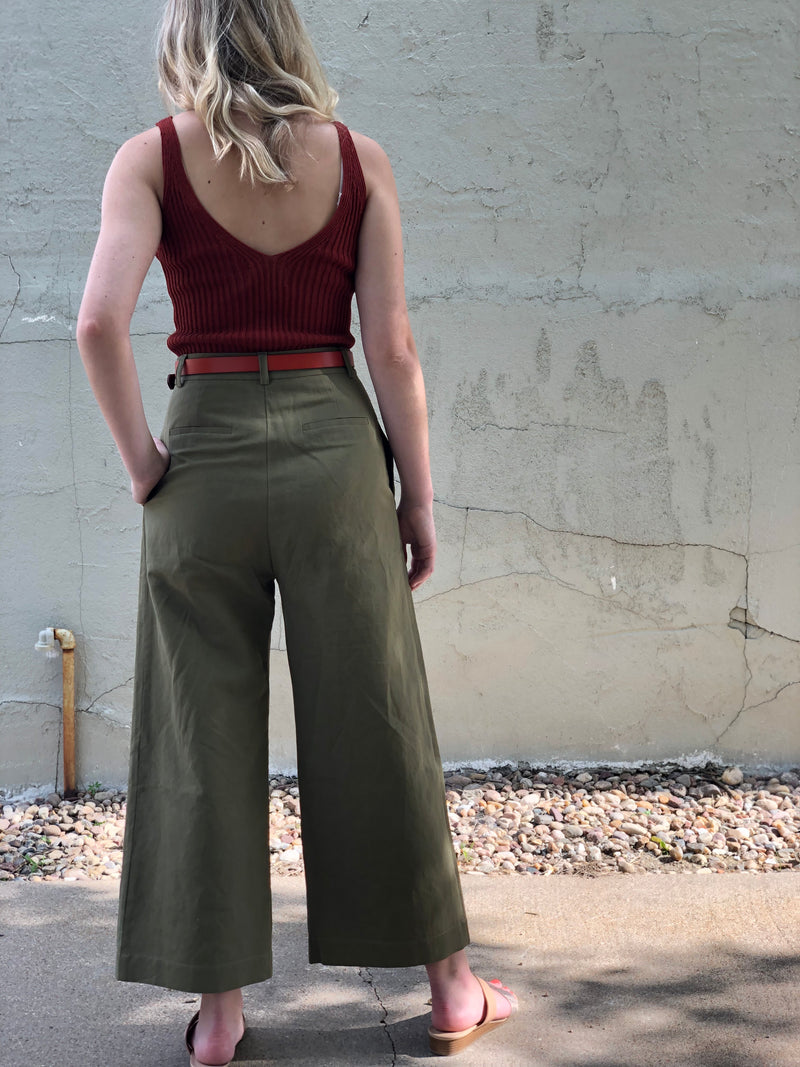 Back of pants on a model outdoors. Model is also wearing a rust colored tank and belt.