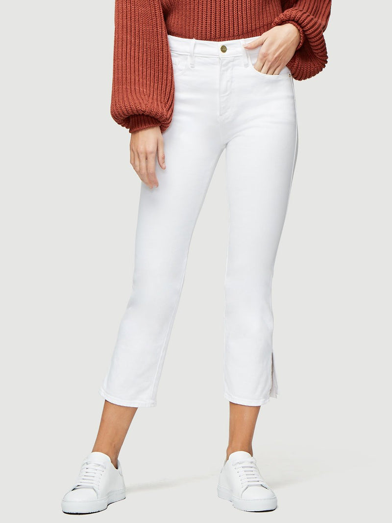 Front of jeans on model wearing white sneakers and a rust sweater.