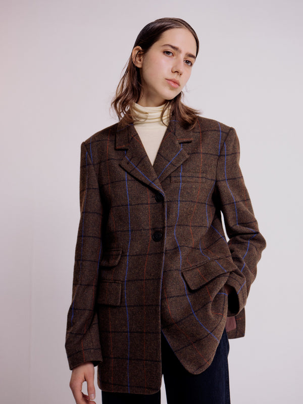 A front view of the Plaid Tailored Jacket by Mijeong Park. This jacket features red and blue thin contrasting plaid stripes. It also features a single breasted button front, peak lapels, and two fold-over front pockets.