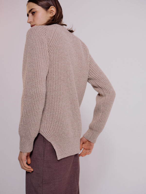 A back view of the Grandpa sweater in taupe. This shows the side slit on the bottom band, as well as, the details of the knit.