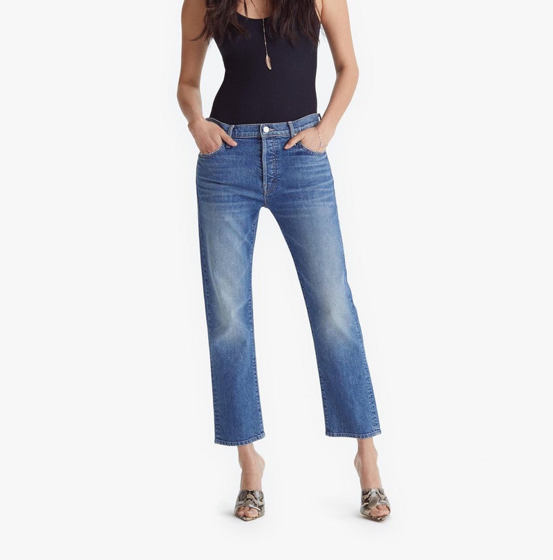 Front of jeans on model wearing a black tank and heels with hands in pockets.