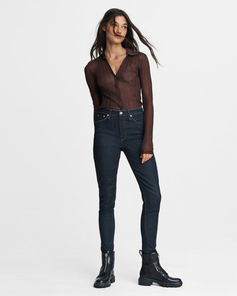 An outfit featuring the Nina Skinny jean. The model has been styled with black combat boots, a sheer brown button down, and the nina skinny jean.