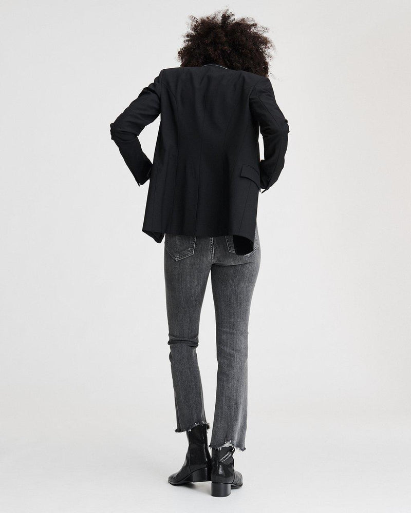 Back of blazer on a model also wearing grey jeans and black boots.