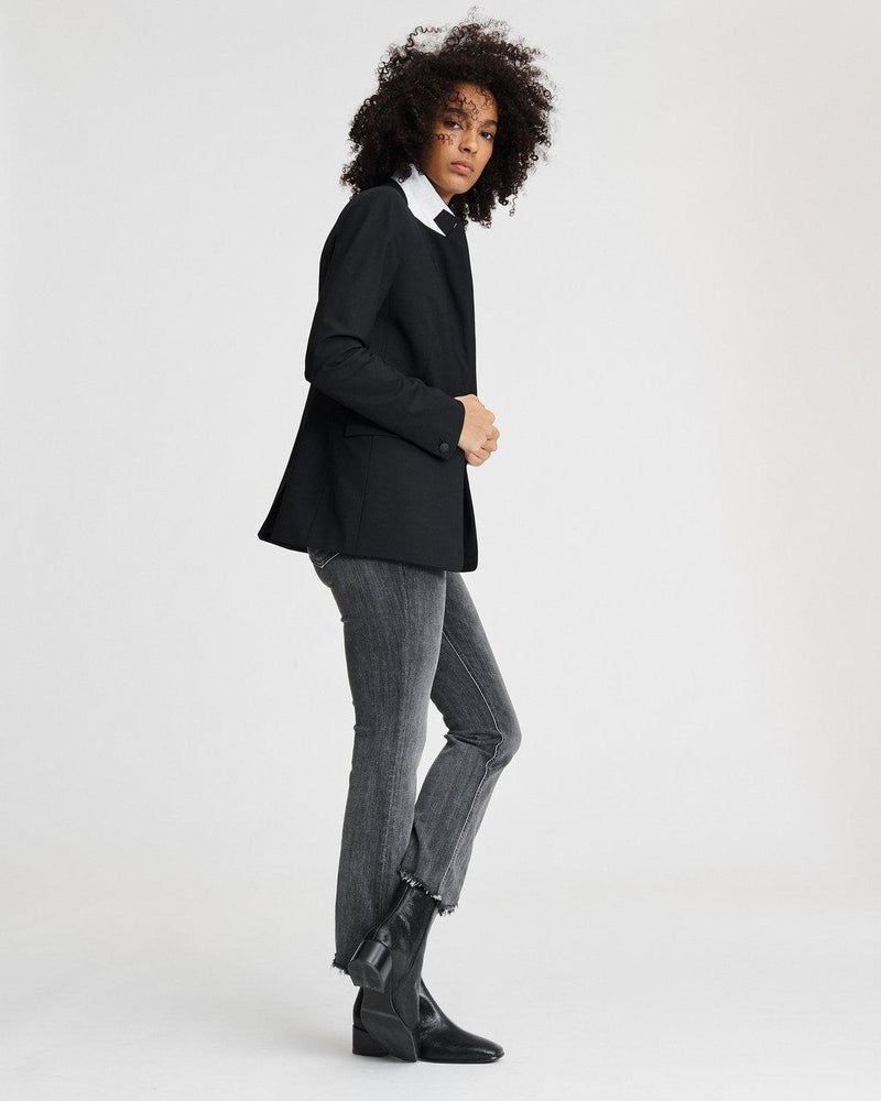 Side of blazer on model with a popped collar, paired with grey denim and black boots.