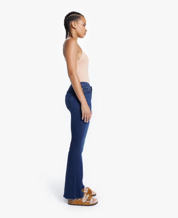 A side view of the model wearing the Mother Weekender Fray Jean. In this picture you can see the 20 inch leg opening at the bottom of the leg.