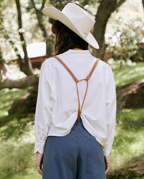 Back of blouse on model wearing suspenders, hat and blue pants.