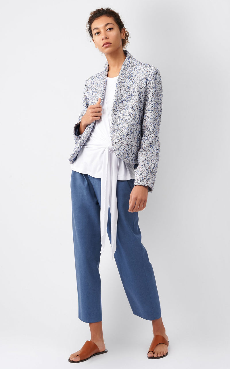 Front of jacket on model wearing a white top and blue pants.