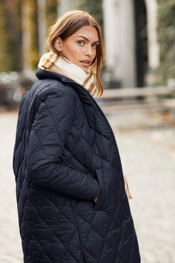 Side of coat on model wearing a scarf.