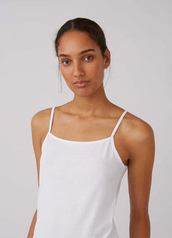 Front of white cami on model, cropped to show strap details.
