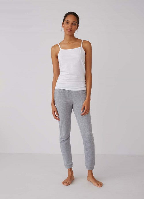Full body shot of model wearing white cami and grey pants.