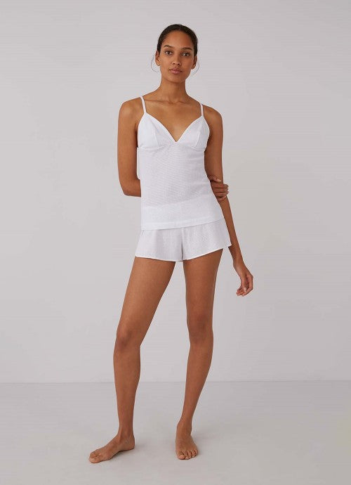 Front of white cami on model also wearing matching white shorts.