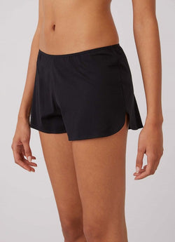Cropped photo of black shorts on model to show front of shorts and slit on the side of the leg.