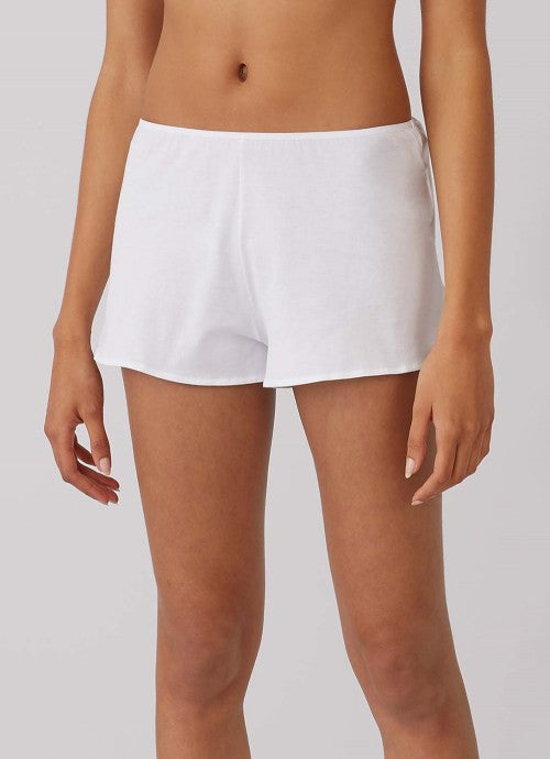 Cropped photo of the front of white shorts on a model.
