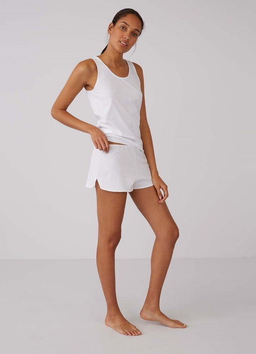 Full body photo of model wearing a white tank top and white shorts.