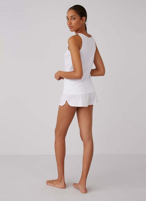Back of white tank on model also wearing matching white shorts.