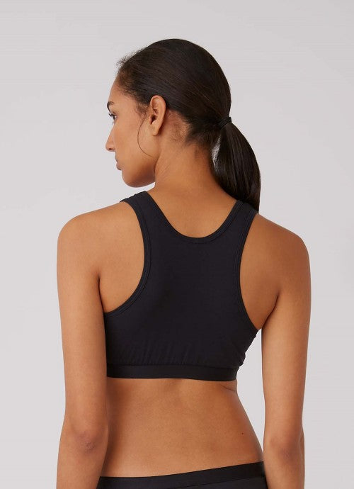 Photo of back of black crop top worn by a model, photo cropped at the model's waist.