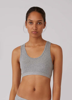 Front of grey crop top on model, photo cropped at model's waist.