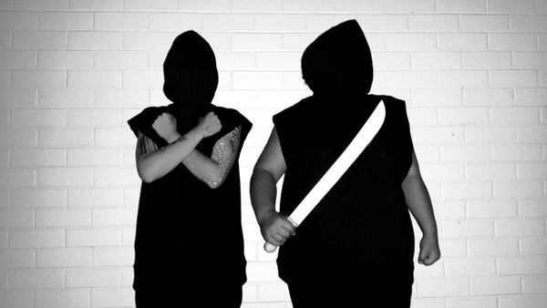 Two people standing in front of a white brick wall wearing their black sleeveless hoodies back to front with their faces covered. One is holding his arms across his chest in an x shape and the other is holding a white machete in their right hand.