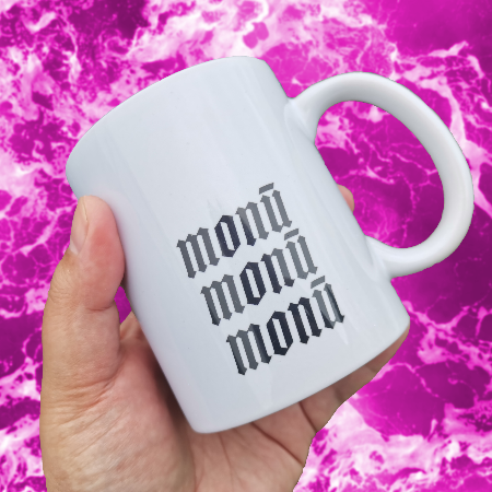 A brown hand holds a white mug with the words monū monū monū printed on it in black. In the background is pink and white ocean waves.