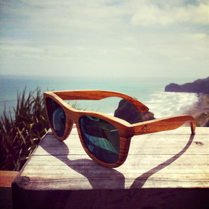 The Nomad style from Sticks Wooden Sunglasses with aqua gold lenses at the beach