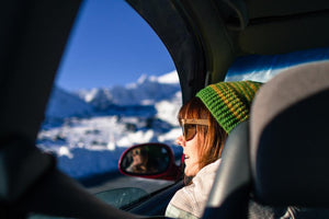 Woman wearing Sticks Nomad Wooden Sunglasses looking out car window at the snow