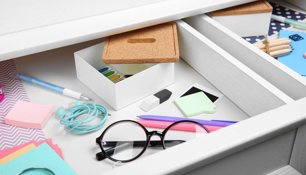 Open desk drawer with office supplies