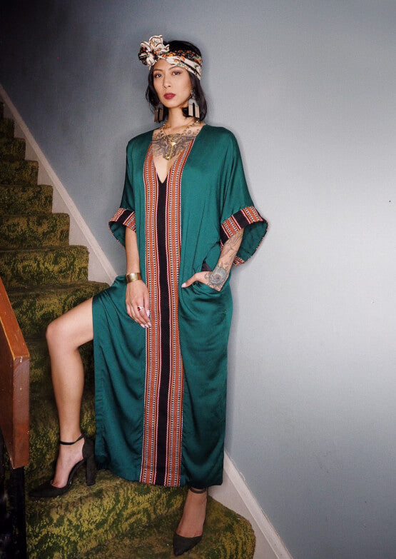 VINTA Kaftan in Emerald Green; worn with green pumps and silk scarf head wrap. Model's hand in pocket.