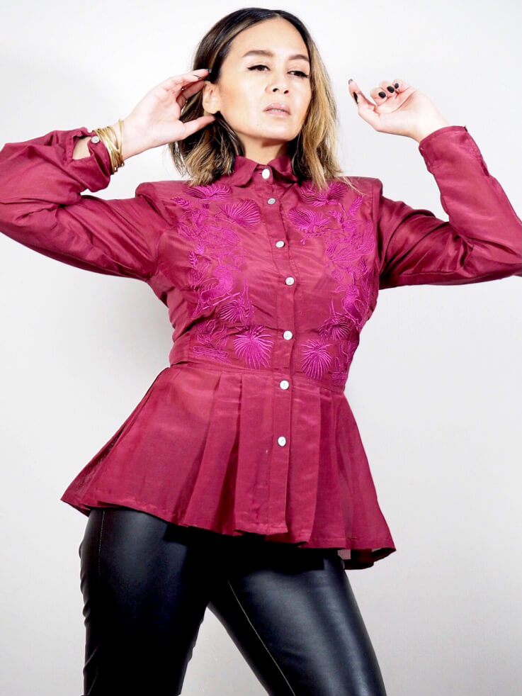 VINTA Peplum Barong in burgundy, with vibrant burgundy thread embroidery. Top is styled with black, liquid leggings. Model's arms are raised, emphasizing the subtle shoulder pads.
