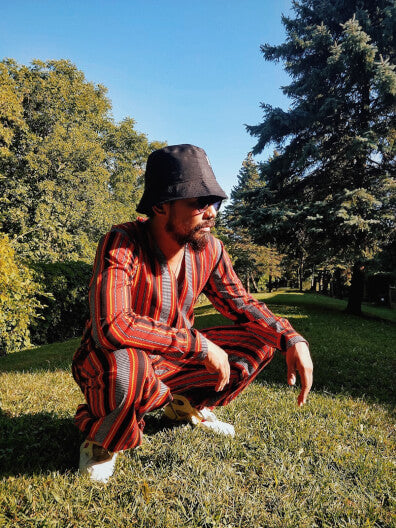 VINTA Unisex Printed Ifugao V-Neck Shirt, Styled with VINTA Printed Ifugao Track Pants and Black Bucket Hat, Male Model Crouched