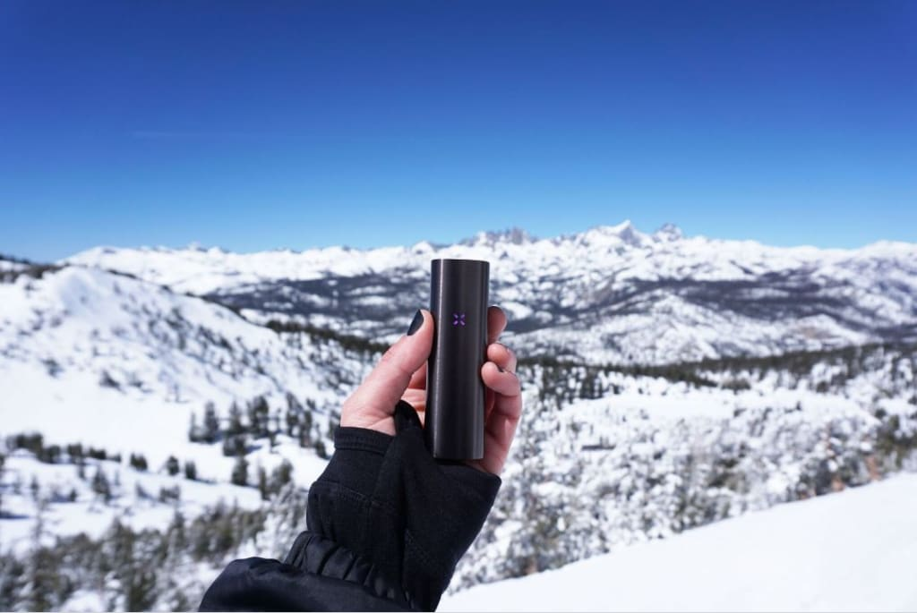 An adventurer holds up the PAX 2 portable vaporizer with snow-capped mountains in the background.