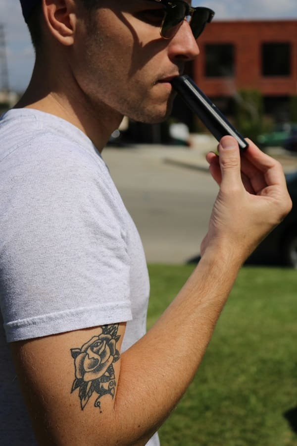 A man stands in the grass vaping with the sleek, stealthy G Pen Pro