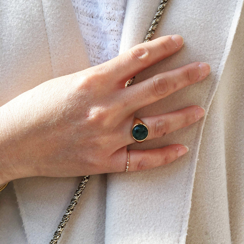 photo of a hand wearing the signet round in gold vermeil with a emerald in the ring finger