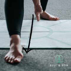 Standing separate leg head to knee pose from the bikram hot yoga series using the archer hot yoga towel, the best hot yoga towel for aligning your foot placement in this yoga posture