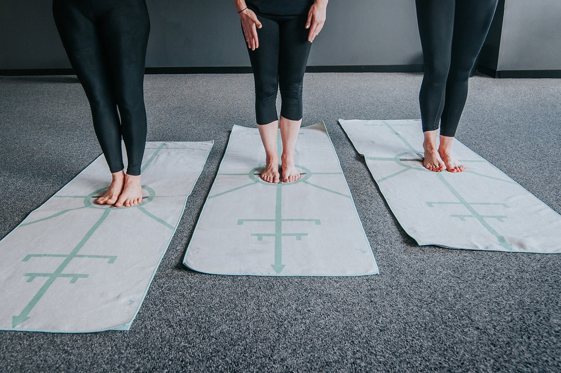 Bikram yoga students standing in the centre circle of the archer hot yoga towel before beginning half moon pose with hands to feet pose.