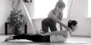 teacher adjusting yoga student