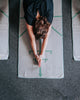 bikram yoga student doing half tortoise pose with archer yoga towel